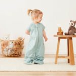 A toddler standing beside a chair, wearing an ergoPouch Sleep Suit Bag 1.0 Tog in Sage colour
