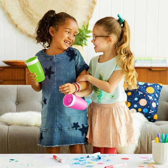 Two little girls, each holding a Munchkin Miracle® 360° Cup