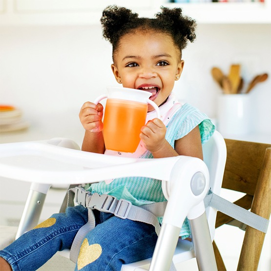 Toddler sitting on a highchair, holding an orange Munchkin Miracle® 360° Trainer Cup
