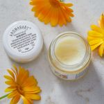 Aromababy Barrier Balm 10g tub lifestyle shot with flowers