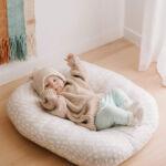 Baby lying on a Cushii Lounger - Wanderlust Oatmilk on the floor
